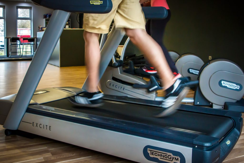man running on a treadmill inside a fitness studio named technogym