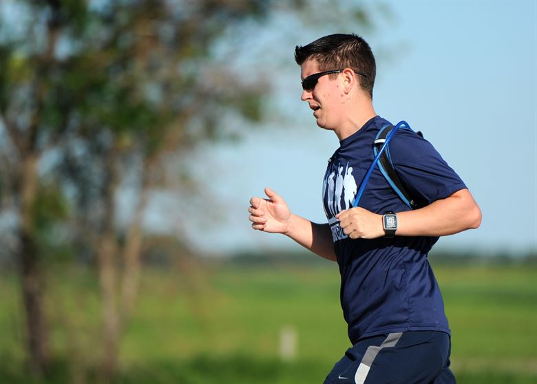 man wearing blue shirt and shades running while wearing hydration running vests